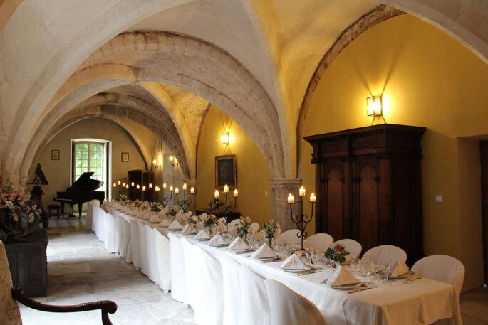 Une table dressé pour un mariage dans une abbaye avec de sublimes voûtes et une architecture gothique
