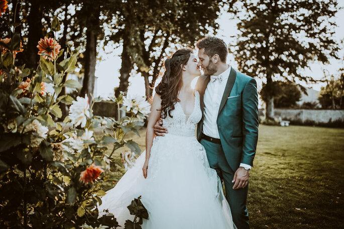 Un couple de mariés pendant sa séance photo dans les jardins fleuris du château.