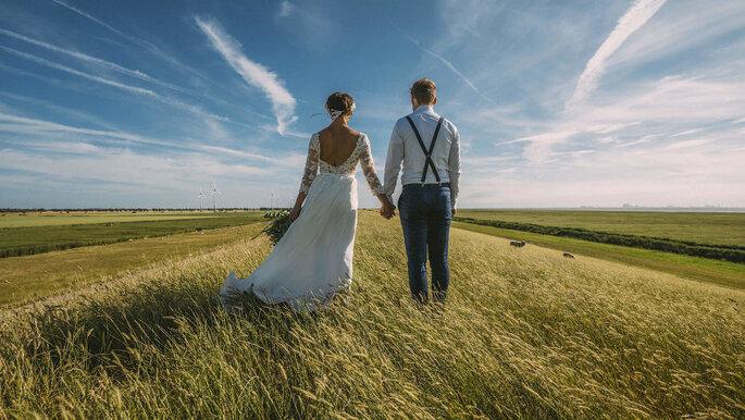 Ein Brautpaar steht Hand in Hand auf einem Feld.