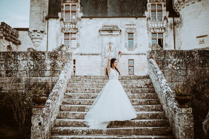 La mariée descend les escaliers en pierre de la propriété.