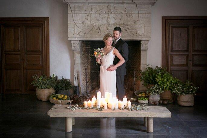 Deux mariés enlacés devant la monumentale cheminée du Domaine de Quicampoix avec des bougies disposées devant eux pour une ambiance hygge