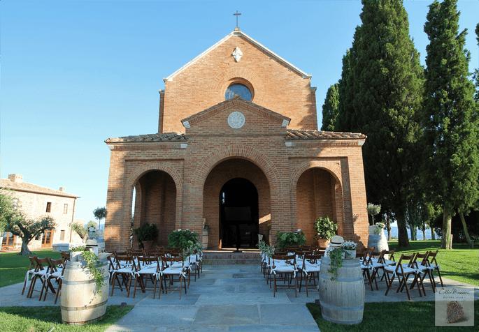 Des chaises disposées pour une cérémonie laïque en extérieur devant la façade d'une église