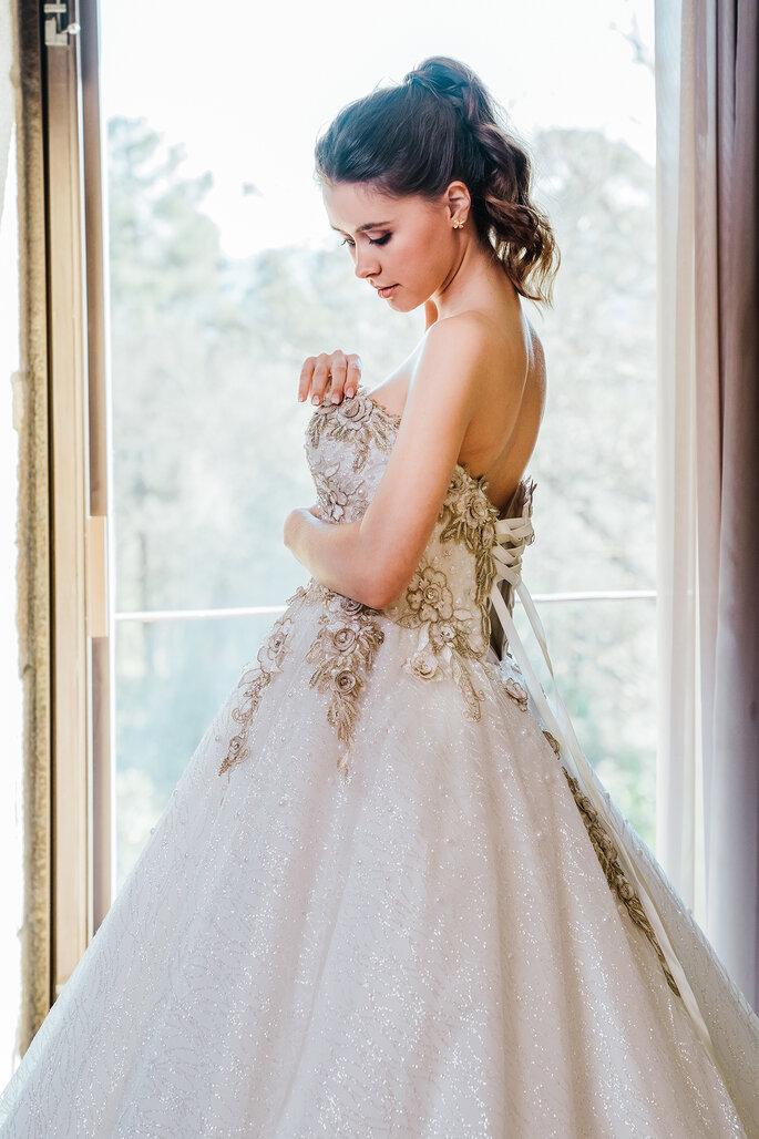 noiva à janela com vestido princesa com bordados de predaria e rabo de cavalo