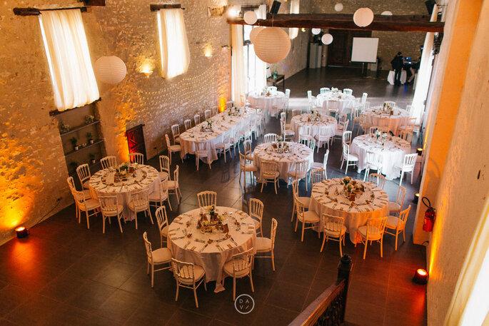 Salle de réception aménagée pour un mariage, avec des tables décorées et des murs de pierres apparentes