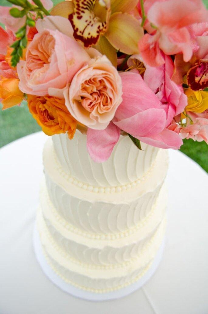 Pastel de boda alto, blanco con decoración de flores naturales en la parte superior