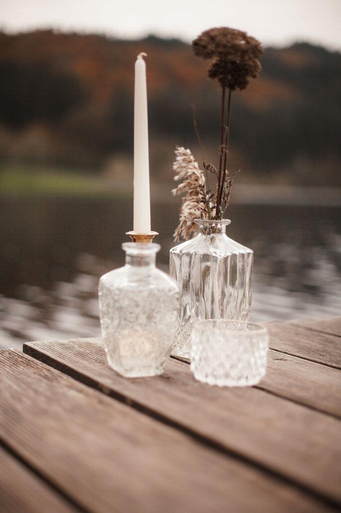 Kleine und große Vasen auf einem Bootssteg mit getrockneten Blumen.