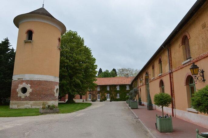 Une douve et une tour de château ainsi que la façade d'un lieu de réception immense, propice à l'organisation d'un mariage