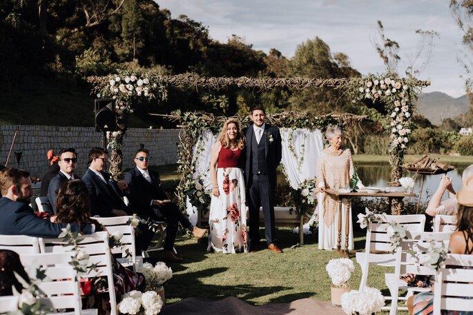 Decoración campestre de ceremonia con arco de flores