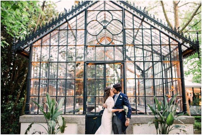 Noivos a beijarem-se à frente de uma estrutura de ferro e vidro