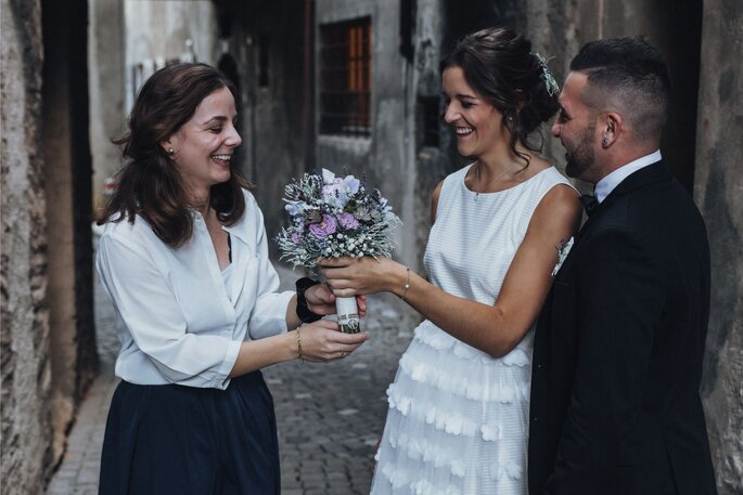 Die Braut bekommt den Brautstrauß überreicht.