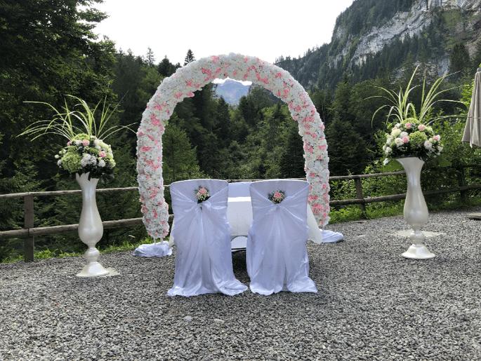 Zwei Stühle mit weißen Hussen stehen vor einem rosanen Blumenbogen. Im Hintergrund sind die Berge
