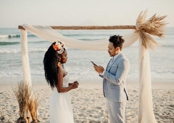 Casal afro trocando votos em cerimônia  na praia