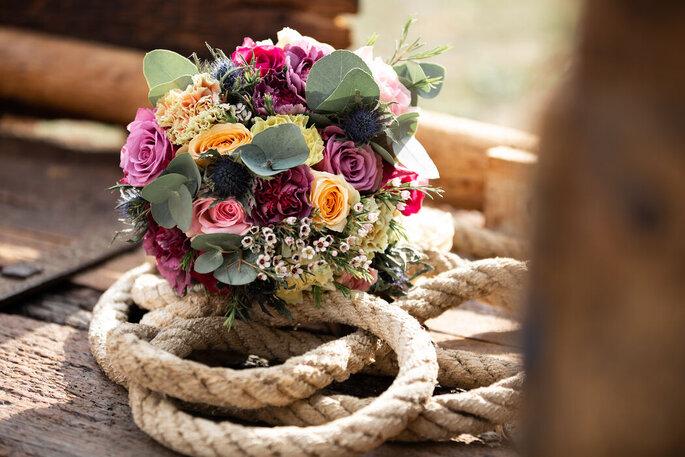 Bouquet de mariée composé de roses de couleurs disposé sur une corde