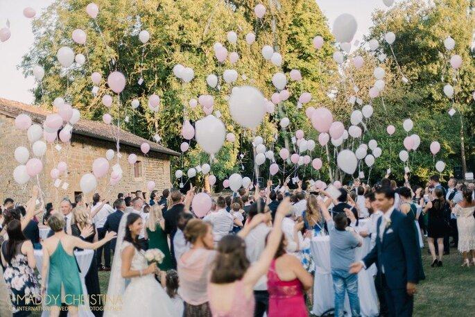 Après la cérémonie de mariage, les invités lâchent des ballons roses et blancs vers le ciel.