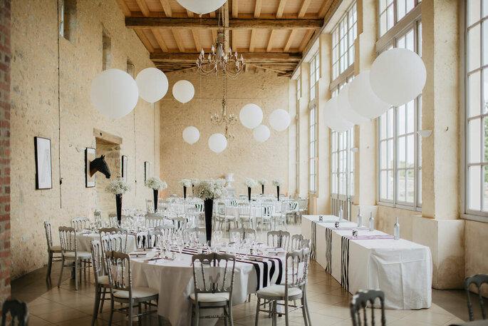 Une salle de réception lumineuse et authentique décorée avec des ballons blancs.