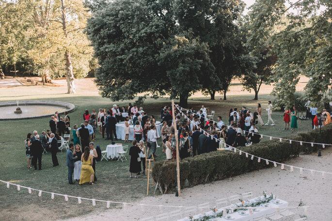 Vin d'honneur dans un parc, les invités du mariage profitent des extérieurs arborés
