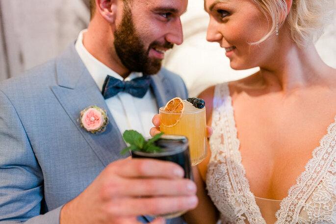 Das Brautpaar stößt mit Cocktails an und schaut sich dabei tief in die Augen.