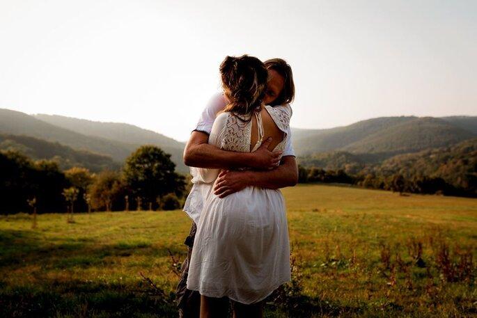 Photo prise au cœur de la nature, d'un couple entrain de s'enlacer avec passion.