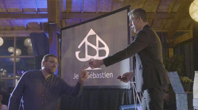 Jean-Sébastien réalise un tour de magie à un invité.