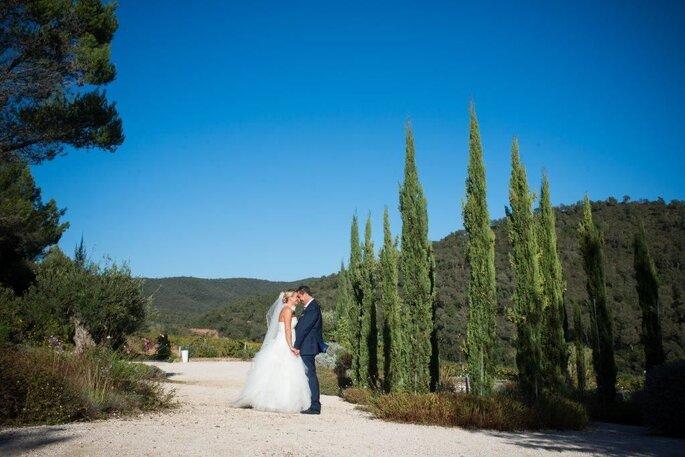 Un couple de mariés complice se fait photographier dans un parc typiquement provençal