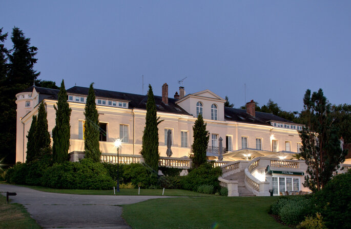 Façade du Domaine de Vaugouard avec ses grands escaliers et ses arbustes en premier plan.