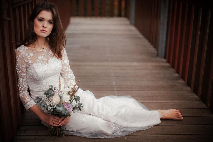 Brautlook im Vintage-Boho-Look: Die Braut trägt ein langes Brautkleid und ist barfuß.