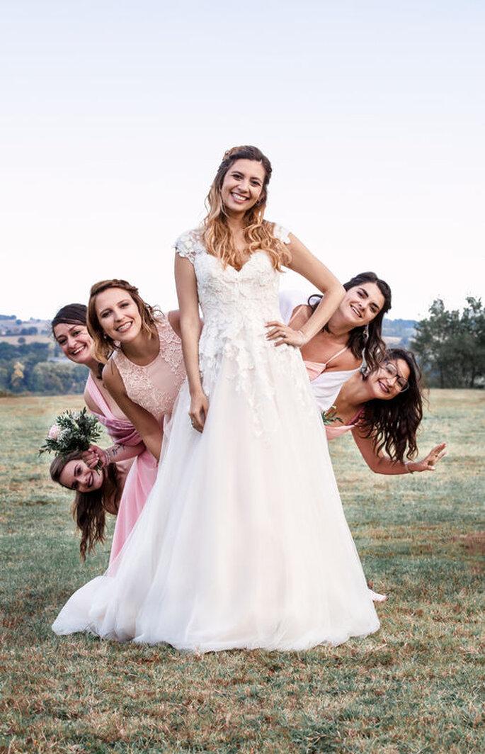 Une mariée avec ces demoiselles d'honneur caché derrière elle en train de poser dans un champs