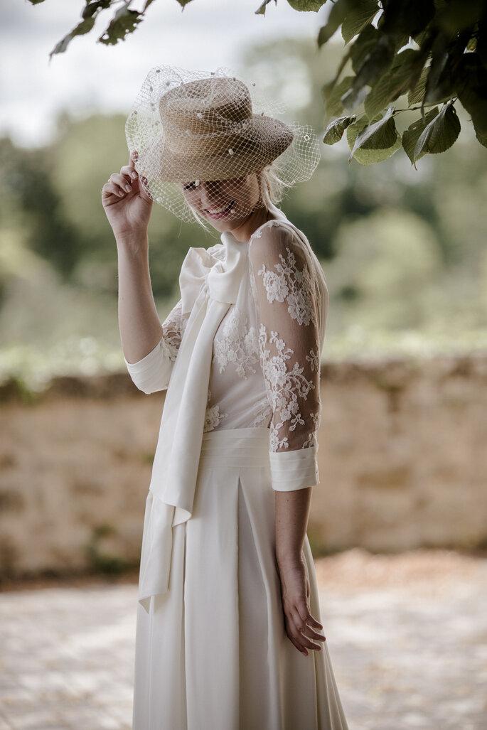 Une mariée avec une jupe et chemisier de mariage et un chapeau