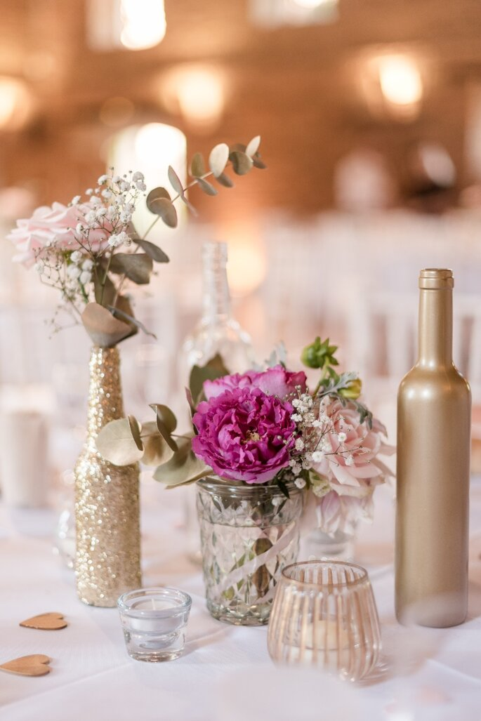 Décoration composée de fleurs rose et de bouteilles dorée pour une ambiance de mariage glamour et girly