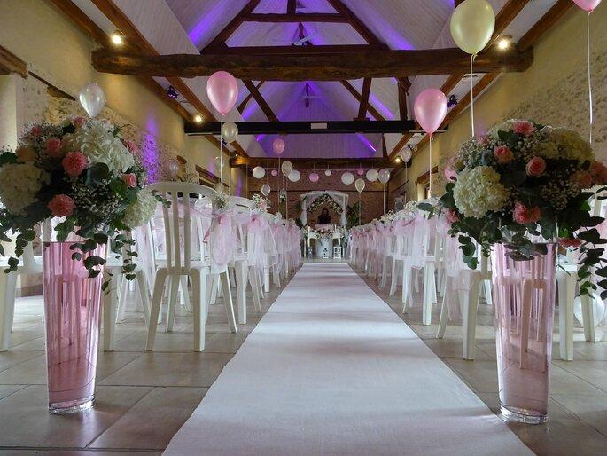 Salle d'intérieur avec poutres en bois apparentes décorée de chaises et d'une arches blanches ainsi que de bouquets et de ballons pour une cérémonie laïque