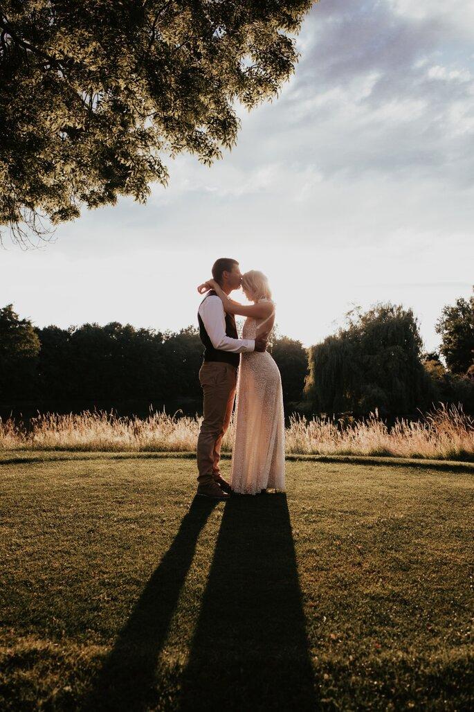 Deux mariés photographiés au milieu d'un parc