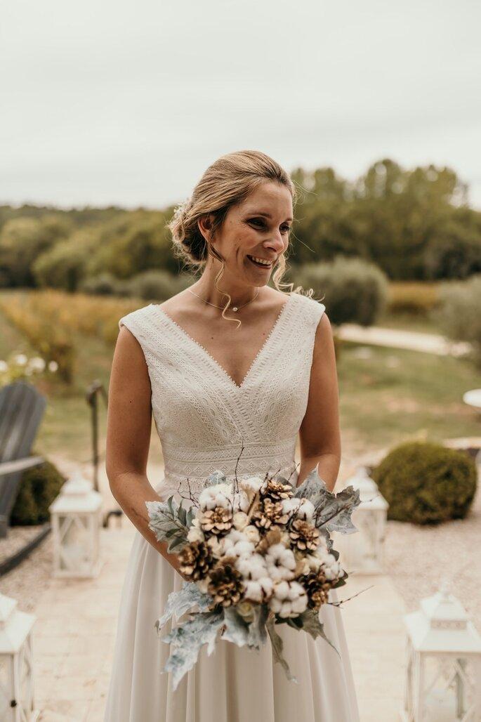 Bouquet à la main, la mariée arrive sur son lieu de réception, sourire aux lèvres