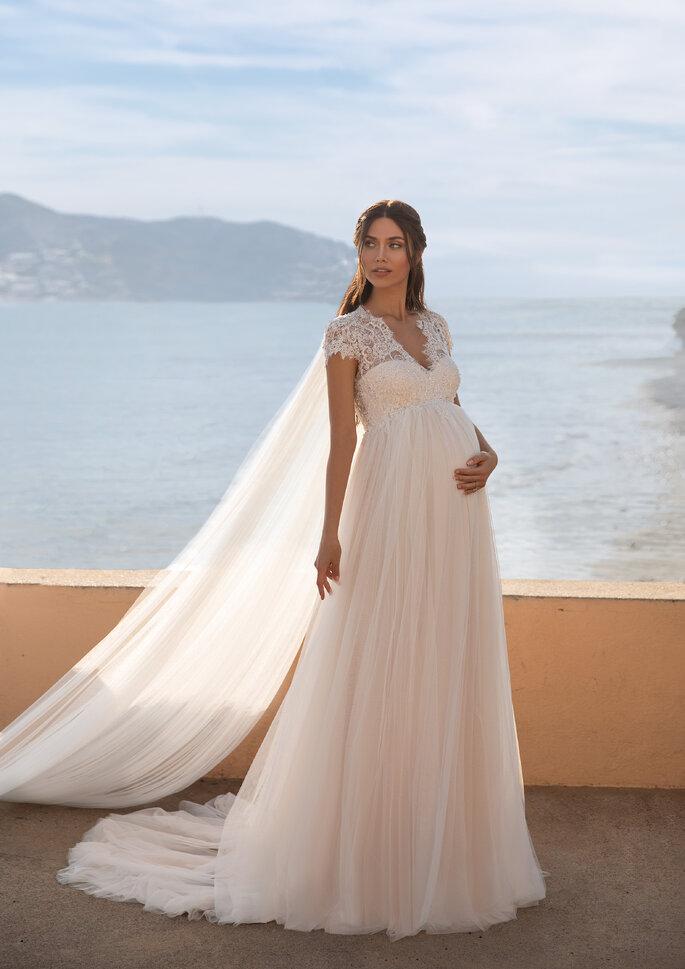 Vestido de noiva corte império, decote coração e capa da coleção Cápsula Maternidade Pronovias 2021 Cruise Collection