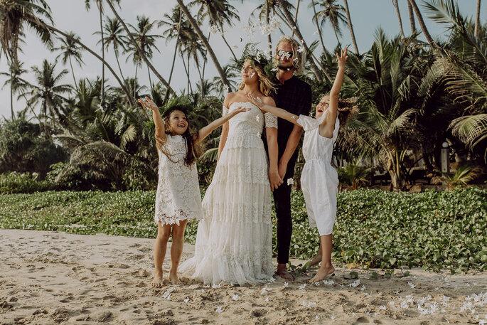 Brautpaar und Töchter stehen am Strand und jubeln.