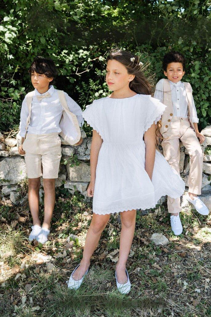 Une fille et deux garçons habillés en tenues pour enfants pour un mariage