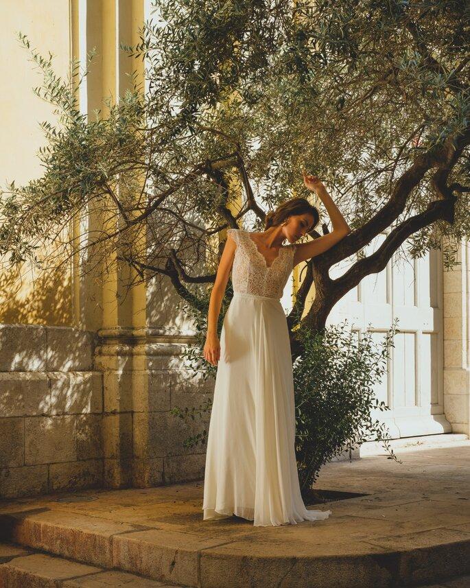 Une mariée portant une robe fluide et féminine dans une cour intérieure près d'un olivier