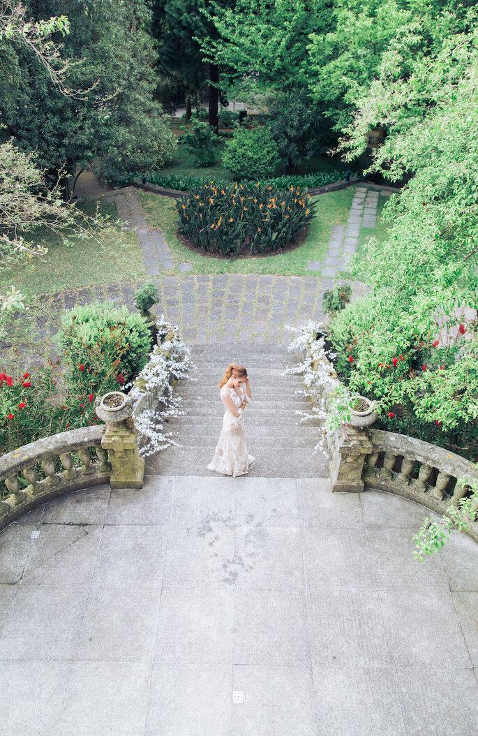 La mariée dans les jardins verdoyants de son lieu de réception.