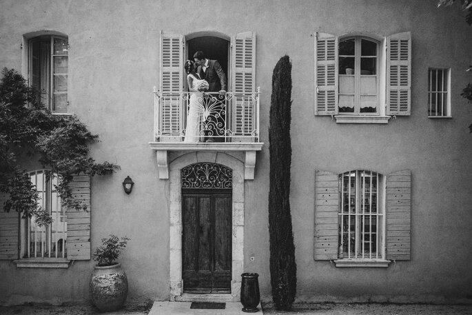Façade en noir et blanc du Château Grand Boise, avec des mariés s'embrassant au balcon
