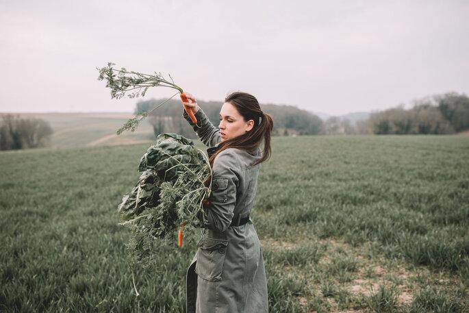 Un agricultrice récolte des carottes dans un champ
