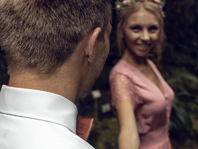 Eine Braut mit rosa Kleid lächelt ihren Bräutigam in einem Garten an.