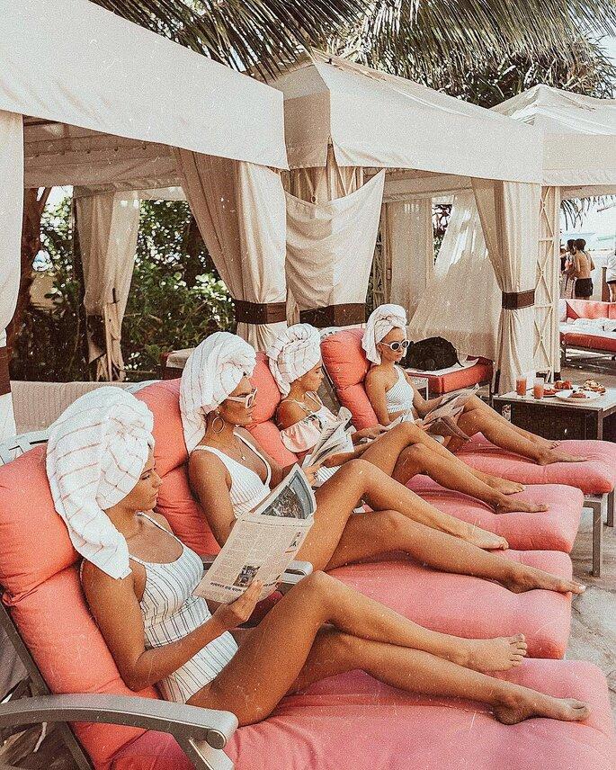Mädels auf Liegestühlen am Pool liegend