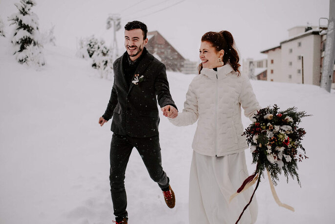 Deux mariés en train de courir sous la neige dans une station de ski lors d'un mariage en hiver