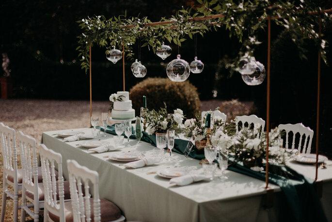 Une table à une réception de mariage décorée dans un style bohème-chic avec des lanternes, des fleurs et des végétaux suspendus