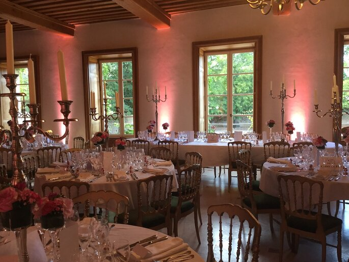 Une salle de réception de mariage lumineuse, des chandeliers ornent les tables