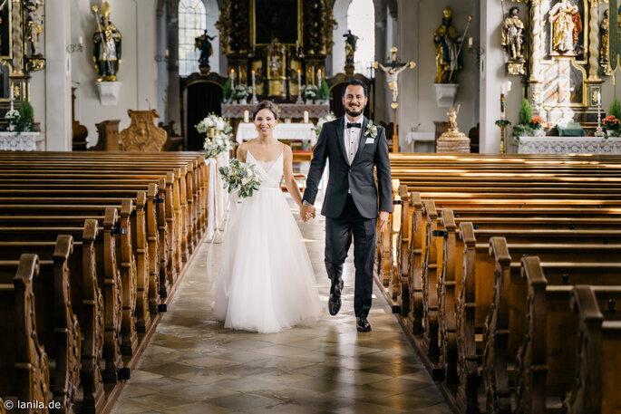 Brautpaar auf dem Weg aus der Kirche nach Trauung