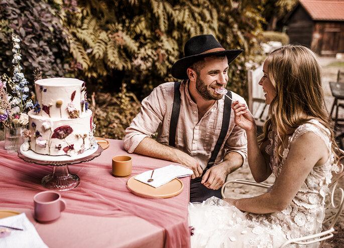 Brautpaar AM tisch sitzend mit Hochzeitstorte