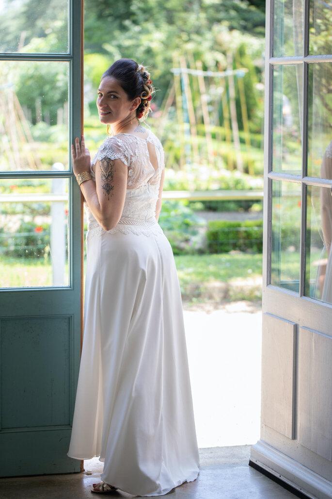 Une mariée appuyée sur une fenêtre regarde l'objectif sourire aux lèvres. Elle porte une robe de mariée revêtant un dos en dentelle.