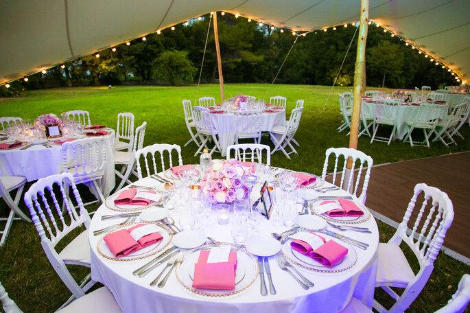 Table dressée dans les tons roses et blanc pour un mariage sous une tente de location