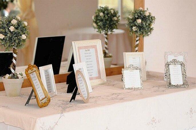 Cadres disposés sur une table, rien de tel pour le plan de table ! - Source : vintage-flair