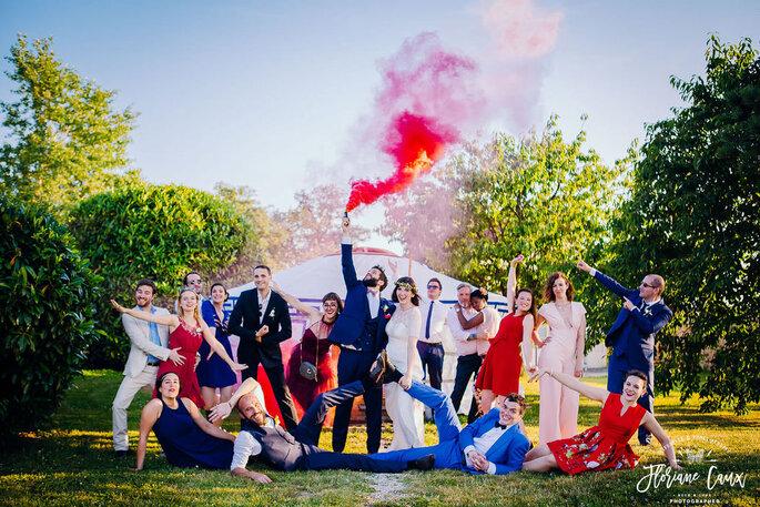Des mariés et leurs invités posent devant une yourte avec un fumigène rouge